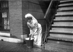 Dienstbode [dienstmeid, huishoudster] in Amsterdam bezig met het dweilen van de stoep. Amsterdam, 1912.